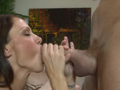 A brunette that has huge tits is performing a blow job