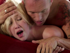 A blonde with a sexy set of tits is getting fucked from behind