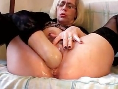 Filthified granny pushes fist up her mature cunt