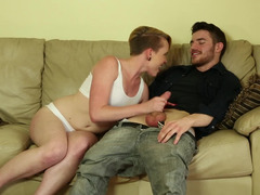 A blonde with short hair sucks a large dick on the sofa