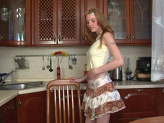 A blonde is in the kitchen, sitting down on a large rubber dildo