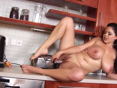 A bitch with large tits fools around in the kitchen nude
