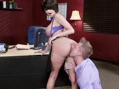 A busty milf with big silicone filled udders is fucked in the office