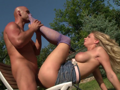 Blonde with large tits is getting her sexy feet licked outdoors