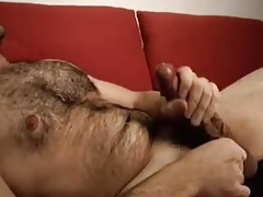 Hairy man stroking and shooting cum