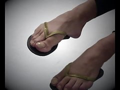 Cd show flip flops dangling and feet with painted toes nails