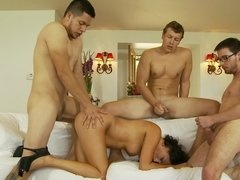 A hot raven haired girl is getting fucked by several men in an orgy