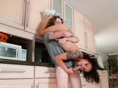 A chick that has a hat on is fucked in her pussy in the kitchen