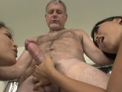 Two women are with an old dude and they are sucking a large cock