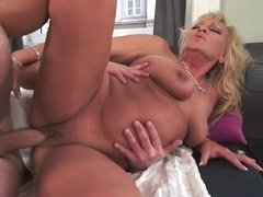 A granny with large tits sits on a large cock while on the bed
