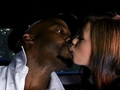 A horny chick is in the car with a black dude, licking his cock