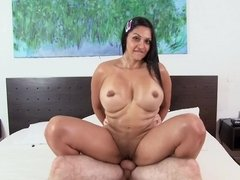 Two large fake tits are shaking on the bed as the Latina is rammed