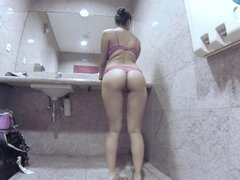 Asian woman with large natural boobs is fucking a dude in the bathroom