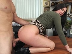 Sexy slut is shaking her ass on the office table in front of us