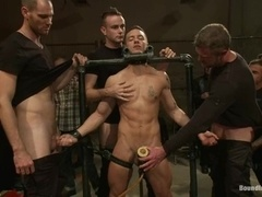 Handsome gay gets shackled and fucked in gay group BDSM scene