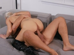 Glamorous blonde woman in high boots fucks Keiran on the couch