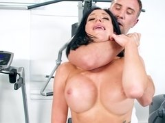 A chick with silicone tits is getting fucked in the gym