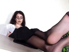 Secretary takes off shoes and moreover puts her feet in nylons up