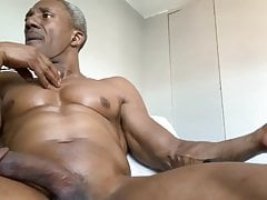 Muscled mature guy smoking while stroking